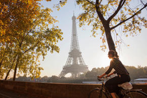 Cyclists in the early morning pass by the iconic Eiffel Tower in Paris, France