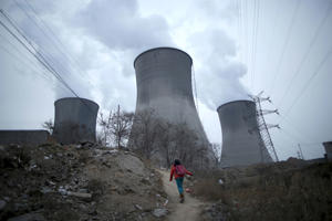 A girl makes her way to her house which is next to cooling towers of a coal-fired power plant in Shijiazhuang, Hebei province, China, January 28, 2015.