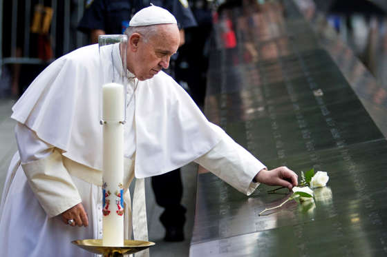 Pope Francis places a white rose at the South Pool of the National September 11 Memorial & Museum in New York on Friday, Sept. 25, 2015. John Minchillo/AP