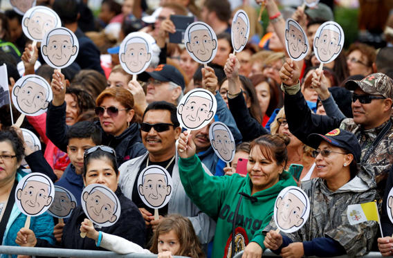 People wave images of Pope Francis as they wait for him to arrive for a Mass at the Cathedral Basilica of Saints Peter and Paul in Philadelphia, Saturday, Sept. 26, 2015.