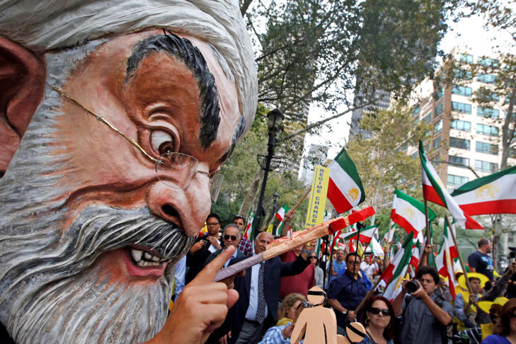 A protester wearing a large mask bearing the likeness of Iranian President Hassan Rouhani attends an anti-Rouhani rally outside United Nations headquarters ahead of the leader's address to the 70th session of the U.N. General Assembly, Monday, Sept. 28, 2015, in New York.