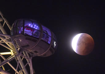 A supermoon is seen during a lunar eclipse behind pods of the London Eye wheel in London, September 28, 2015.