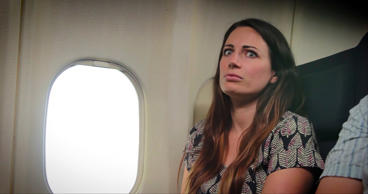 Still image from video of a concerned woman on an airplane.