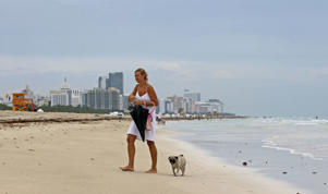 A woman walks her dog on the beach on a cloudy day at the South Beach area of Miami Beach, Florida.