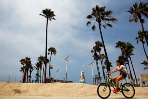 A girl rides a bike on the strand at Venice Beach in Los Angeles, California.