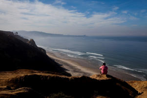 A visitor looks out over Blacks Beach in San Diego, California.