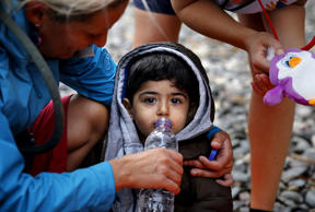 Volunteers give water and toys to an exhausted Syrian refugee child soon after he and his family arrived on the Greek island of Lesbos in an overcrowded dinghy after crossing a part of the Aegean Sea from the Turkish coast September 22, 2015