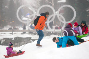 Tourists sled down a hill in the Whistler Olympic Plaza in Whistler, British Columbia, Canada.