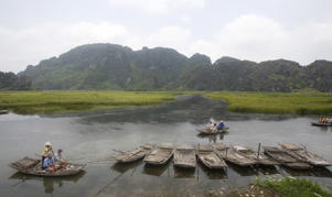Tourists travel on bamboo boats at the Van Long natural reserve, Vietnam.