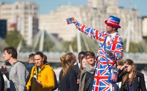 An entertainer on stilts speaks to tourists in Westminster, London.