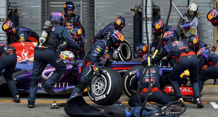 Red Bull Formula One driver Sebastian Vettel of Germany is attended to by his crew during a pit stop during the Brazilian F1 Grand Prix at the Interlagos circuit in Sao Paulo November 24, 2013. REUTERS/Nelson Almeida/Pool (BRAZIL - Tags: SPORT MOTORSPORT F1)