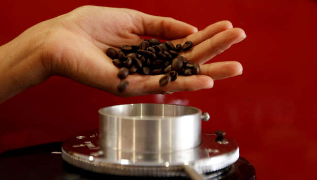A waitress pours coffee beans into a grinder before she prepares an expresso at a coffee bar in Sao Paulo in this February 8, 2011 file photo. Coffee drinkers in Brazil, America, Eastern Europe and the Middle East are expected to down more arabica beans in their brew in the coming year, reported October 30, 2013, as cheap prices attract additional demand for the higher spec product. A surplus from top grower Brazil after two successive bumper crops helped drag arabica prices to a four-and-a-half-year low this week, which is likely to prompt roasters to increase the use of the bean in their blends. Picture taken February 8, 2011.