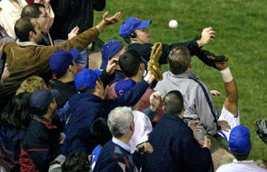 In this Oct. 14, 2003 file photo, Chicago Cubs left fielder Moises Alou's arm is seen reaching into the stands, at right, unsuccessfully for a foul ball along with a fan identified as Steve Bartman, left, wearing headphones, glasses and Cubs hat, during the eighth inning against the Florida Marlins in Game 6 of the National League Championship Seriesin Chicago.