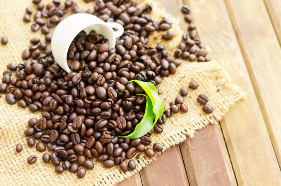 coffee beans with white cup and green leaves.