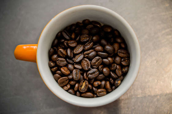 Coffee beans sit in a cup during a class at the Barista Basics Coffee Academy in Sydney, Australia, on Monday, May 25, 2015. Once stereotyped as a land of meat pie-eaters and Foster's lager-swillers, Australia has developed a A$4 billion ($3.2 billion) coffee-drinking market that devours more fresh beans per person than any other country.
