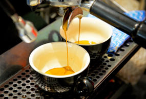 Espresso pours from a machine into cups during a class at the Barista Basics Cof...