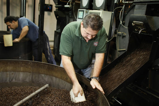MIAMI - MARCH 3: Hernando Vasquez checks beans pouring from the roaster before they are bagged at Colonial Coffee Roasters March 3, 2008 in Miami, Florida. Coffee prices recently hit its highest level in a decade, as continuing weakness in the dollar kept many commodity markets soaring.