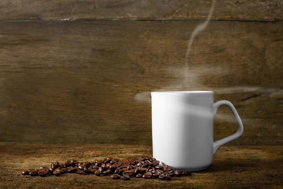 Dia 1 van 19: Cup of coffee with smoke and coffee beans on old wooden background.
