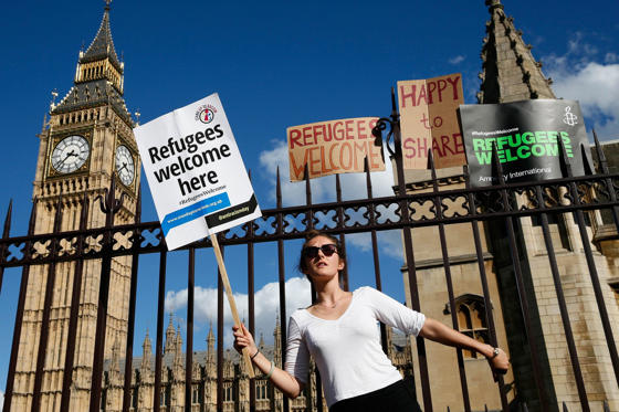 A protester holds on to the railings outside the Houses of Parliament during a demonstration to express solidarity with migrants and to demand the government welcome refugees into Britain, in London, Septembver 12, 2015.