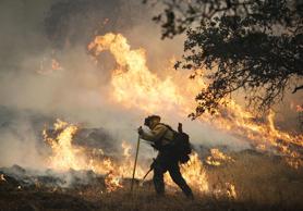 A firefighter lights a back burn along Highway 29 north of Middletown, Calif., S...