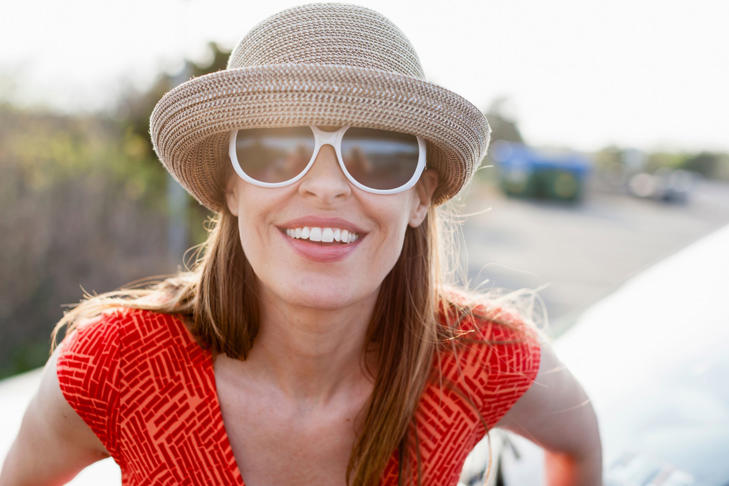 Mature woman wearing sunglasses and sunhat smiling towards camera