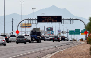 An Arizona Department of Transportation sign gives a hotline number for information on the recent freeway shootings as motorists pass under at the 202/I-10 intersection, Wednesday, Sept. 9, 2015 in Chandler, Ariz. One of three 18-year-old men arrested in hurling rocks at cars with slingshots has denied that they were copying a string of highway shootings that have rattled nerves and heightened fears of a possible serial shooter.