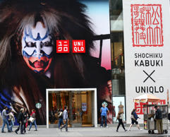 NEW YORK, NY - APRIL 26, 2015: Shoppers walk past the entrance to the UNIQLO store on Fifth Avenue in Midtown Manhattan in New York City. The Japanese casual wear designer, manufacturer and retailer has collaborated with the kabuki company Shochiku to produce a line of clothing inspired by traditional kabuki motifs. (Photo by Robert Alexander/Getty Images)