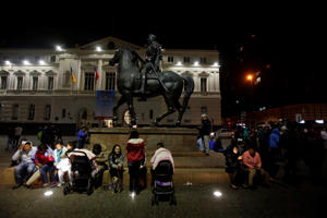 Residents sit next to an equestrian statue, in Santiago's main square after a 8.3 earthquake, in Santiago, Chile, Wednesday, Sept. 16, 2015. The powerful earthquake hit Chile's northern coast causing buildings to sway in Santiago and other cities and sending people running into the streets.