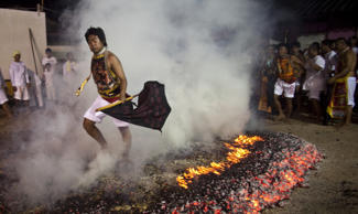 A devotee of Gim Tsu Ong Shrine races across hot coals during a fire walking session at the Vegetarian Festival Sunday, Oct. 25, 2009, in Phuket, Thailand. The annual festival traces its origin back to the early 1800's when Chinese tin miners and others who had been stricken with disease recovered by adhering to a strict vegetarian diet.