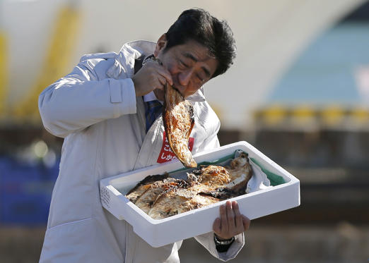 28 枚のスライドの 1 枚目: Japan's Prime Minister Shinzo Abe, who is also leader of the ruling Liberal Democratic Party (LDP), eats a local grilled fish during his official campaign kick-off for the December 14 lower house election, at the Soma Haragama fishing port in Soma, Fukushima prefecture, December 2, 2014.