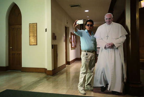 A visitor takes a selfie with a cardboard cutout of Pope Francis at St. Patrick's Catholic Church on September 16, 2015 in Washington, DC.