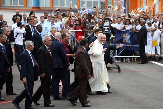 People wave Cuban and Vatican flags as Pope Francis walks with Cuba's President Raul Castro after arriving at Jose Marti International Airport on September 19, 2015 in Havana, Cuba.