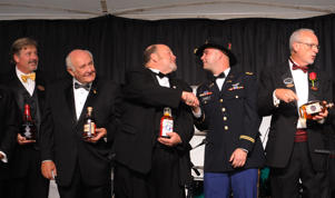 In this photo provided by Patti Longmire, 1st Lt. Clint Hooker shakes hands with Fred Noe, Master Distiller of Jim Beam, at the Kentucky Bourbon Festival Gala.