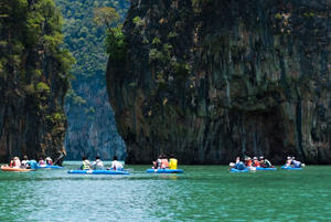 Tourists kayak through limestone cliffs at Phang-nga, Thailand.