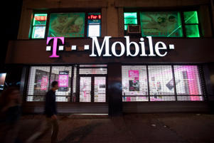 Pedestrians walk past a T-Mobile US Inc. store at night in New York, U.S., on Sunday, July 26, 2015.