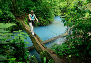 A tourist crosses a bridge over the Celeste river at Tenorio Volcano National Park in Upala, Costa Rica.