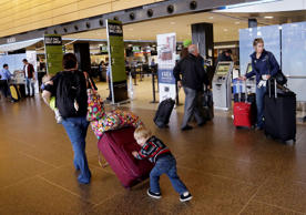 Colin Drummond, 4, pushes luggage from behind as he walks with family members to check-in a relative.