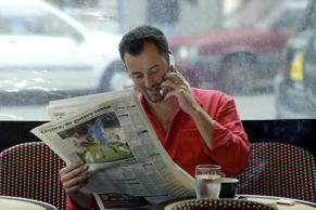 In this file photo, a cafe customer speaks on his mobile phone in Paris, France.