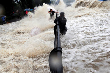 A paramilitary policeman holds onto a fence as tourists dodge tidal waves increased under the influence of Typhoon Dujuan, at the bank of Qiantang river, in Hangzhou, Zhejiang province, September 29, 2015. China ordered tens of thousands of boats back to shore and closed tourist attractions as a typhoon made landfall in the eastern province of Fujian early on Tuesday after leaving two dead and hundreds injured in Taiwan. Picture taken September 29, 2015. REUTERS/Stringer CHINA OUT. NO COMMERCIAL OR EDITORIAL SALES IN CHINA        TPX IMAGES OF THE DAY      - RTS2CK8