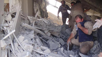This image taken in Wednesday, Sept. 30, 2015 posted on the Twitter account of Syria Civil Defence, also known as the White Helmets, a volunteer search and rescue group, shows the aftermath of an airstrike in Talbiseh, Syria.