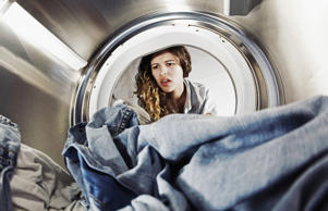 Woman looking into dryer.
