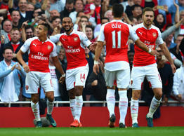 Alexis Sanchez (L) of Arsenal celebrates scoring their third goal with team mates during the Barclays Premier League match between Arsenal and Manchester United at Emirates Stadium on October 4, 2015 in London, England.