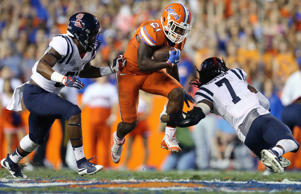 Florida running back Kelvin Taylor (21) rushes for yardage between Mississippi linebacker DeMarquis Gates (31), left, and defensive back Trae Elston (7) during the first half of an NCAA college football game on Oct. 3, 2015, in Gainesville, Fla.
