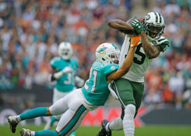 New York Jets' Brandon Marshall, right, catches the ball despite the challenge of Miami Dolphins' Brent Grimes during the NFL football game between the New York Jets and the Miami Dolphins and at Wembley stadium in London, Sunday, Oct. 4, 2015.