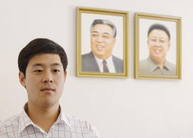 Joo Won-moon, a South Korean citizen who has permanent residency in the United States, leaves a news conference as portraits of North Korea's former leaders Kim Jong Il (R) and Kim Il Sung hang in the background, in Pyongyang, North Korea, in this photo taken by Kyodo September 25, 2015.