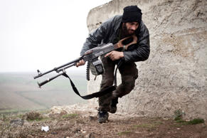 In this December 17, 2012, file photo, a Free Syrian Army fighter takes cover du...