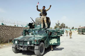 An Afghan soldier raises his hands as a victory sign, in Kunduz city, north of K...