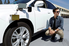 Brian Torcellini, Google team leader of driving operations, poses for photos next to a self-driving car at a Google office in Mountain View, California.