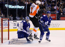 Toronto Maple Leafs goaltender Jonathan Bernier (45) makes a save after being screened by Philadelphia Flyers forward Wayne Simmonds (17) and Toronto Maple Leafs defenceman Stephane Robidas (12) at the Air Canada Centre.