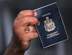 A man displays his Canadian passport. File photo.